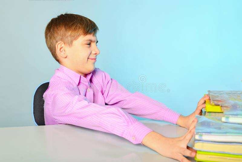 De luie en stomme tiener wil niet leren en duwt handboeken van zich, die bij zijn bureau zitten royalty-vrije stock fotografie