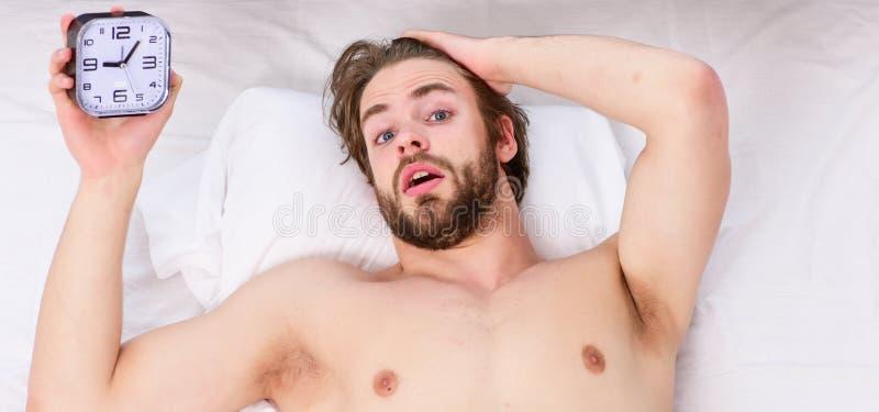 De luie mensen gelukkige ontwaken in het bed die dienen de ochtend met vers ontspannen gevoel in toenemen Mens die rugpijn in voe stock fotografie