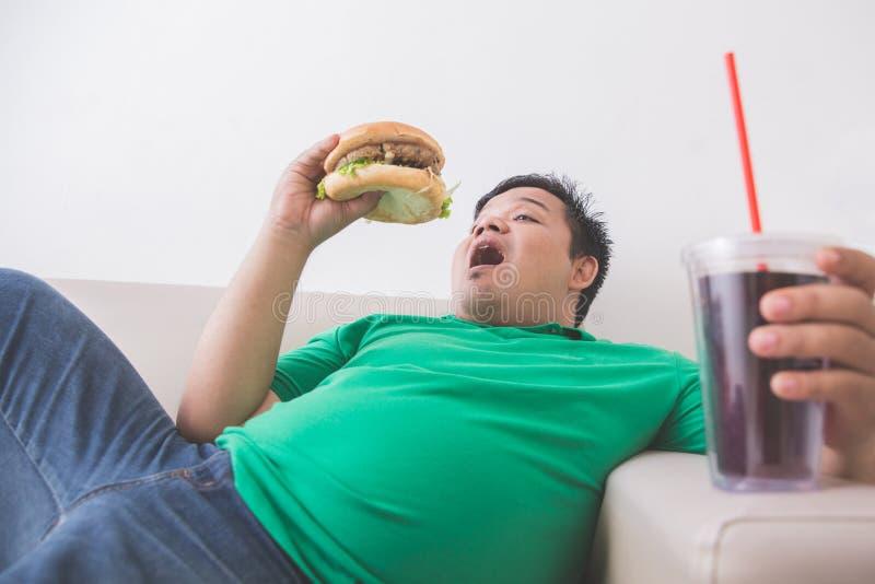 De luie zwaarlijvige persoon eet ongezonde kost terwijl het leggen op een laag stock foto's