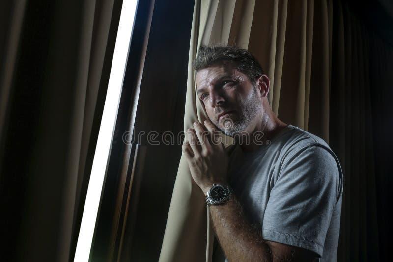 De lumière portrait dramatique à l'intérieur du jeune homme attirant triste et déprimé regardant par la fenêtre de pièce à la mai photos libres de droits