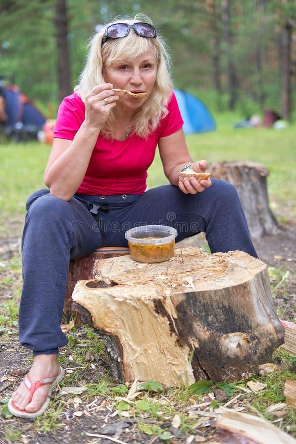 De lunch op een boomstomp, meisje eet soep stock fotografie