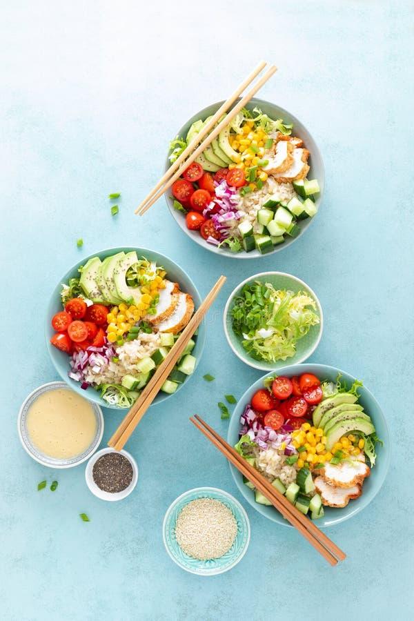 De lunchkommen met geroosterd cgicken vlees, rijst en verse salade van avocado, komkommers, graan, tomaat en ui royalty-vrije stock foto's
