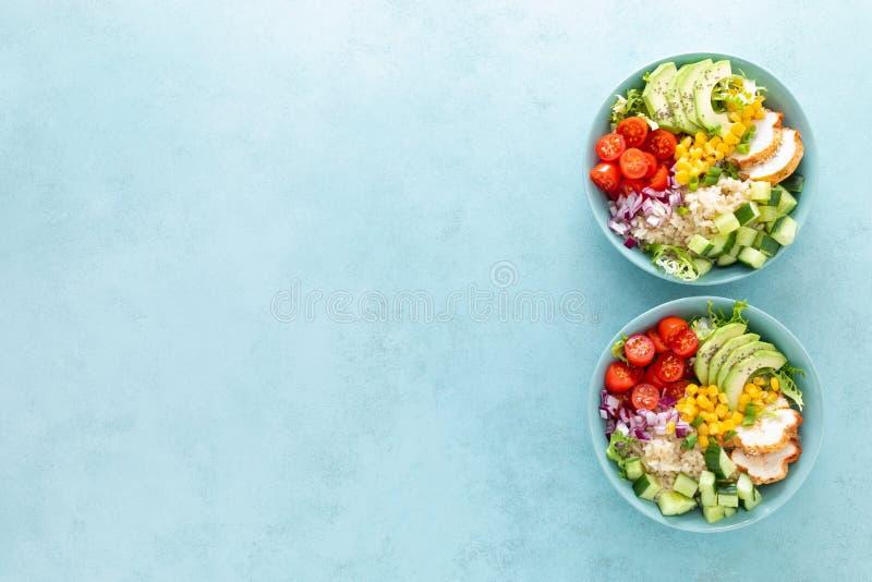 De lunchkommen met geroosterd cgicken vlees, rijst en verse salade van avocado, komkommers, graan, tomaat en ui stock afbeelding