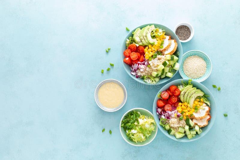 De lunchkommen met geroosterd cgicken vlees, rijst en verse salade van avocado, komkommers, graan, tomaat en ui royalty-vrije stock foto