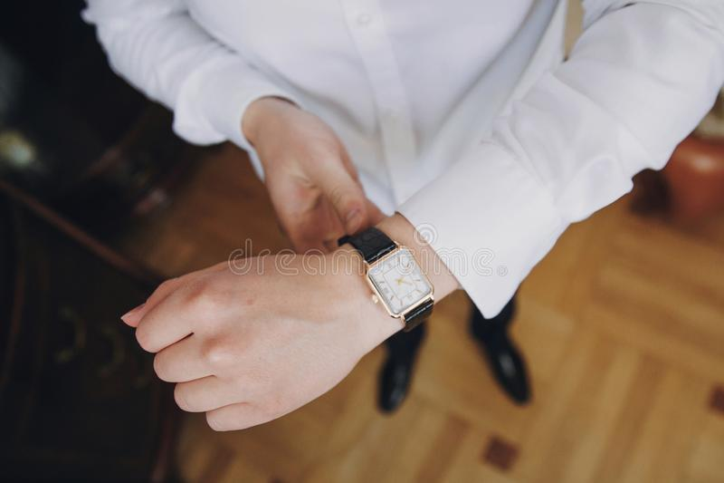 De luxehorloge van de zakenmanholding Modieuze bruidegom die op wit overhemd en horloge zetten, die klaar in de ochtend dichtbij  stock fotografie