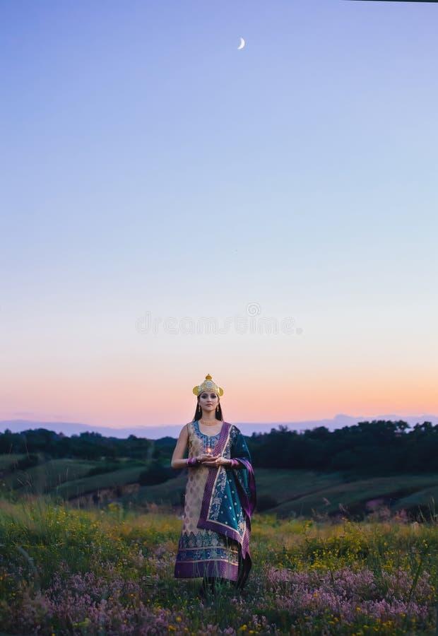 De luxueuze Indische vrouw houdt een kaars in openlucht, in de zonnen stock foto's