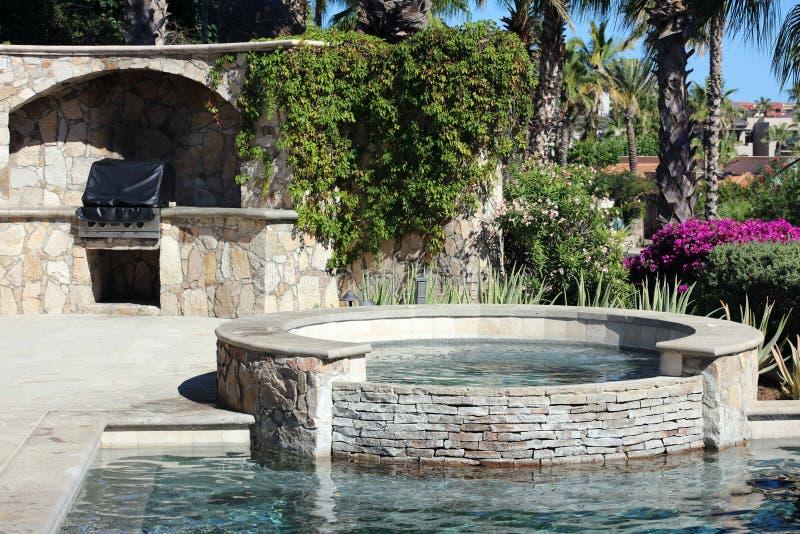 De luxueuze Spaanse Jacuzzi van de stijlpool heet met de eigenschapfontein van het luxewater bij schitterende villa met oceaanmen royalty-vrije stock afbeelding