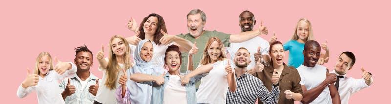 De lyckliga affärskvinnorna och männen som står och ler mot rosa bakgrund royaltyfri foto