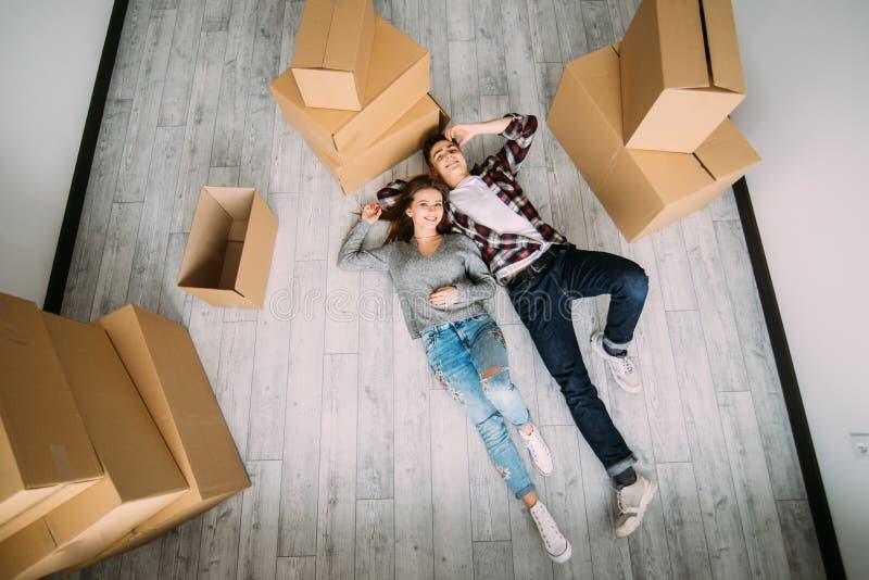 De lyckliga barnparen lägger på de near lådaaskarna för golvet ovanför sikt arkivbild