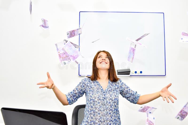 De lyckliga brunhåriga kasten för flickan in i luften fakturerar 500 euro Framgångbegrepp av en ung kvinna royaltyfri foto