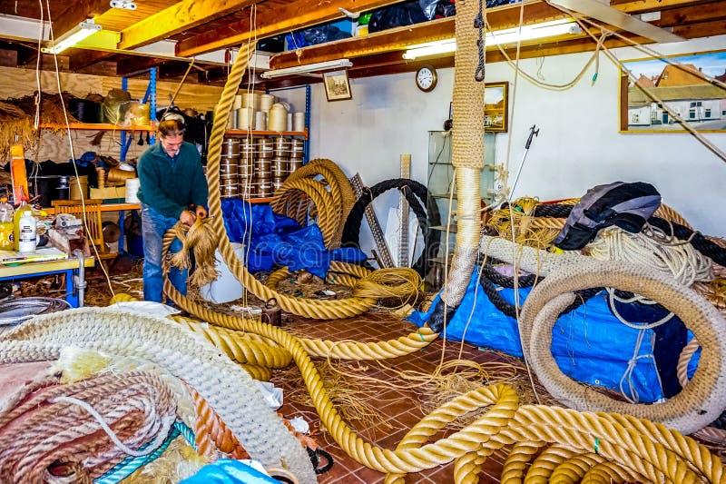 De månghundraåriga teknikerna och hantverket av repdanande på skärm i det historiska holländska fiskeläget av Elburg royaltyfri foto