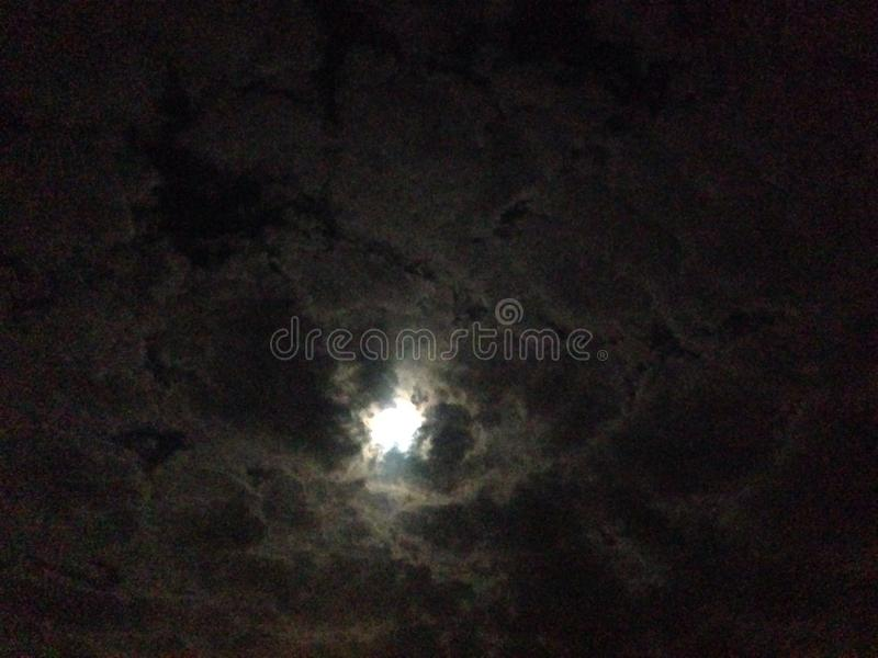 De maan… in een bewolkte nacht stock fotografie