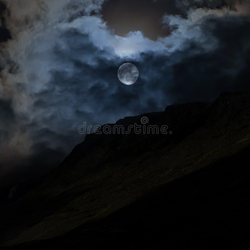 De maan achter de wolken in de nachthemel stock afbeelding