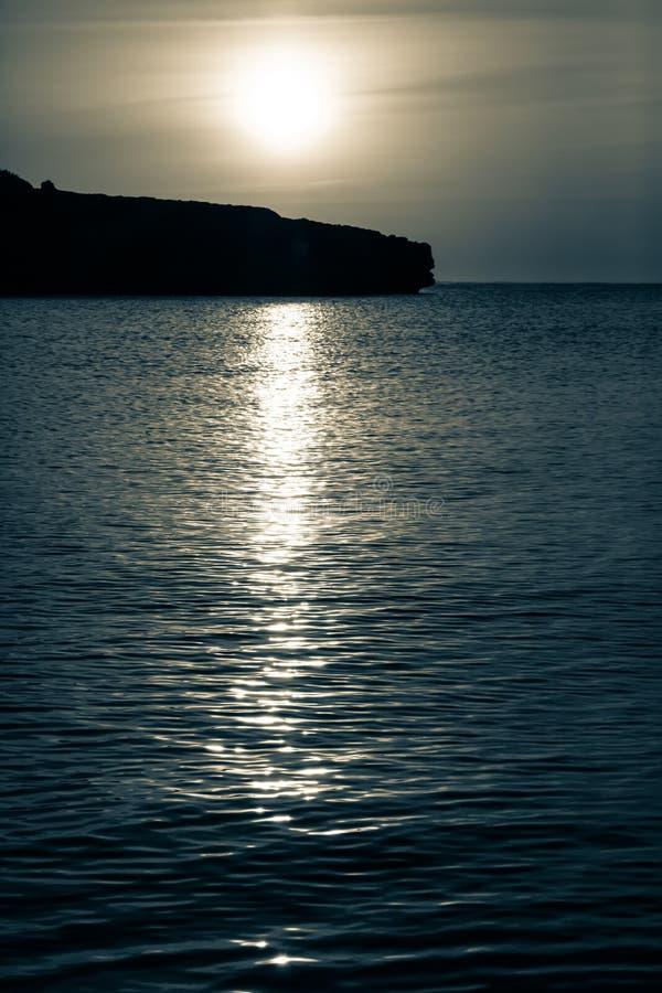 De maan neemt over de oceaan toe bij nacht royalty-vrije stock afbeelding