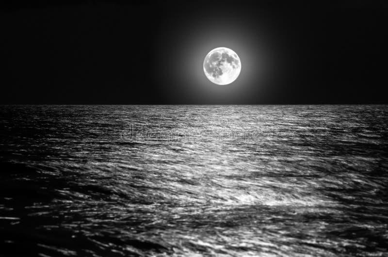 De maan over de overzeese horizon bij nacht maanlicht op de golven stock foto's