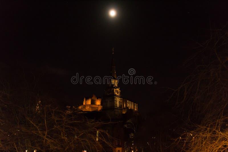 De maan over St Cuthbert en het kasteel van Edinburgh royalty-vrije stock afbeeldingen