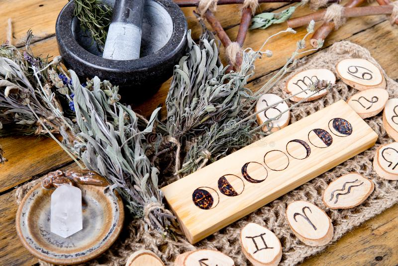 De maanfasen en de astrologische symbolen met kruid beheksen mortier en stamper, met tak pentagram en droge kruidbundels stock foto