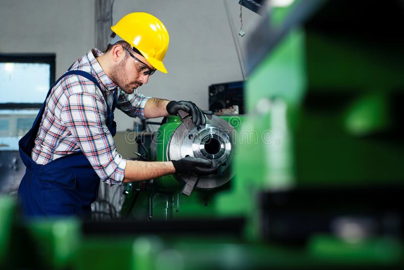 De maatregelendetail van de fabrieksarbeider met digitale beugelmicrometer tijdens het eindigen metaal die aan draaibankmachine w royalty-vrije stock foto's