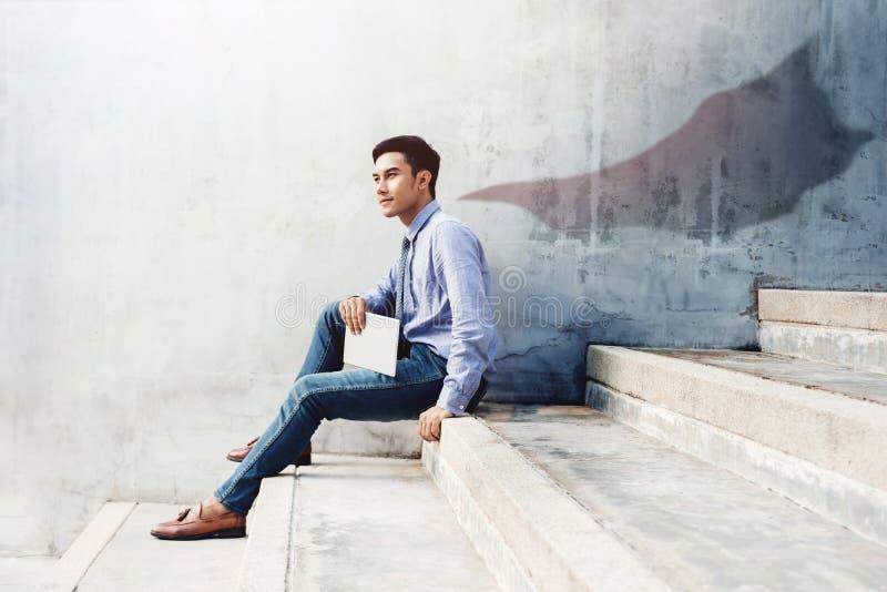 De macht, het Succes en de Leiding in Bedrijfsconcept, Jonge mens zitten royalty-vrije stock afbeeldingen