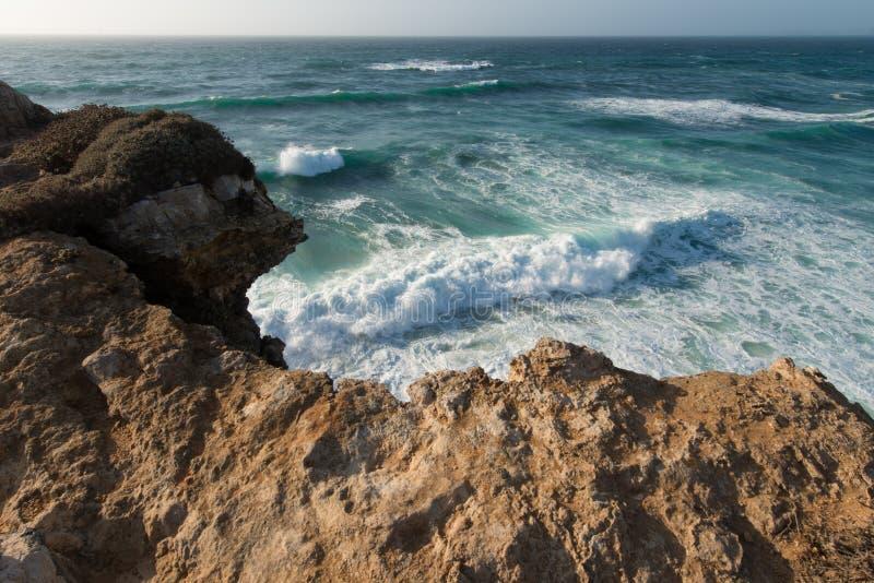 De macht van oceaangolven en Portugese rotsachtige kust van Lagos, Algarve stock foto's