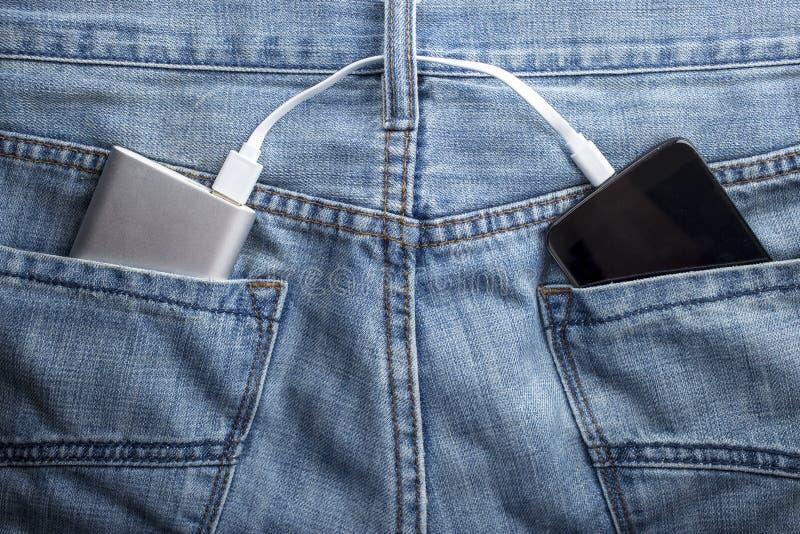 De machtsbank ligt in een achterzak van jeans de mobiele telefoon charg stock afbeelding