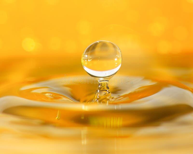 De macroclose-up van de waterdaling, oranje achtergrond stock afbeeldingen