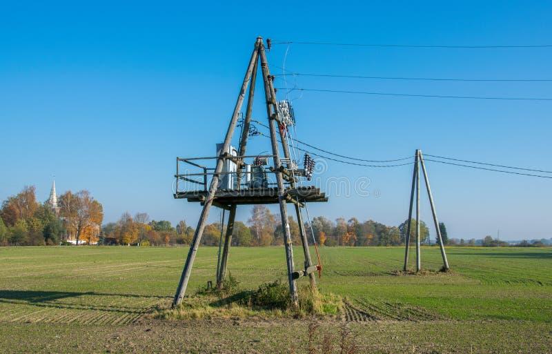De madeira apoia linhas elétricas de alta tensão contra o céu azul Indústria elétrica imagem de stock royalty free