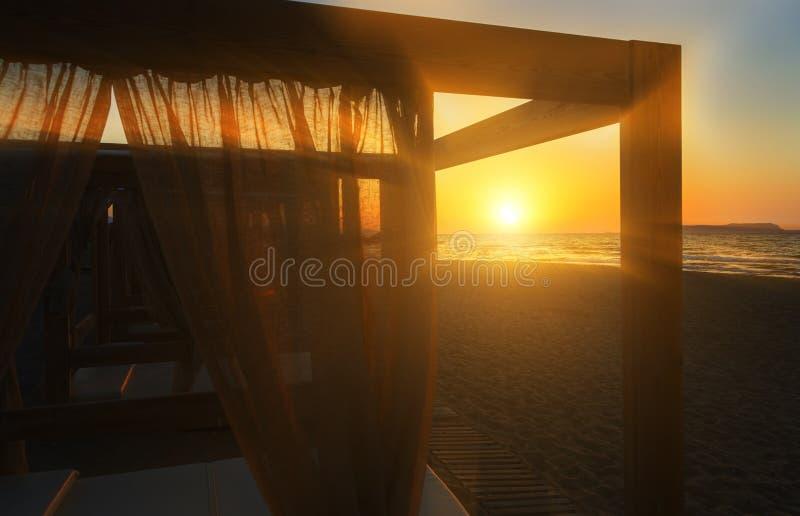 De madera con el puente del gazebo de las persianas en el mar en el cielo de la tarde de la puesta del sol imagen de archivo libre de regalías
