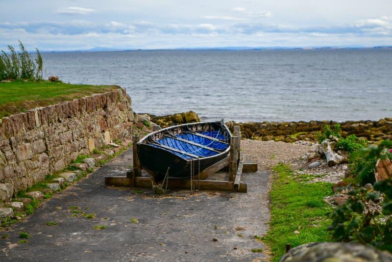 De madera un barco solo por el mar rodeado por piedras y una pared imágenes de archivo libres de regalías