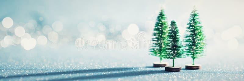 De magische miniatuurbanner van het de wintersprookjesland Altijdgroene Kerstmisbomen op glanzende blauwe achtergrond stock afbeelding