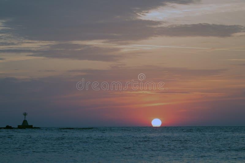 De magiska färgerna av soluppgången - molnig himmel och den sol- skivan som kysser havet arkivbild
