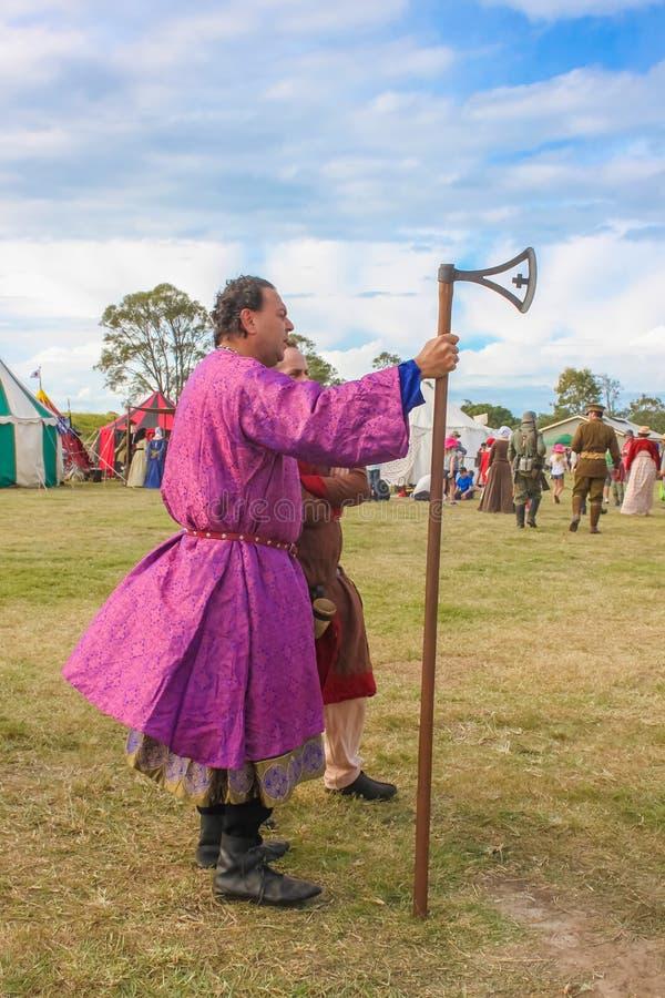 9 de maio de 2014 Brisbane Austrália - homem vestido na veste ornamentado roxa que mantém o machado atrasado da cruz de Viking do fotografia de stock
