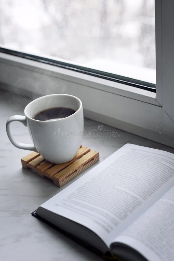 De maison toujours la vie confortable : tasse de café ou de thé chaud et livre ouvert sur le rebord de fenêtre Concept d'éducatio photos stock