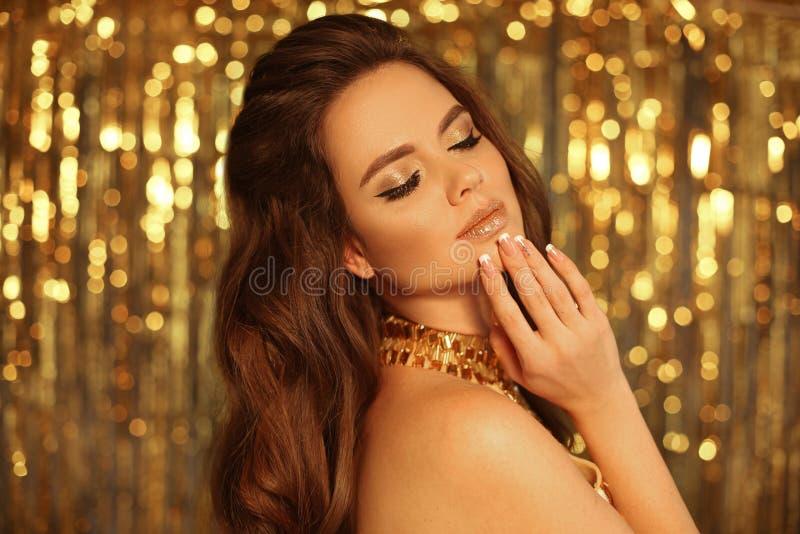 De Make-up van glamouroogschaduwwen Het Meisjesportret van de manierschoonheid op gouden de slingers bokeh achtergrond die van Ke stock foto's