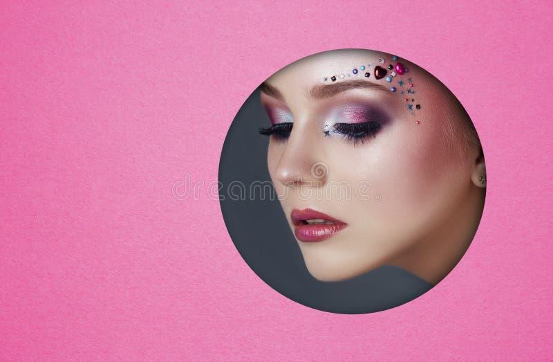 De make-up van het schoonheidsgezicht van een jong meisje in een rond gat van roze document Vrouw met mooie make-up, heldere ogen stock fotografie