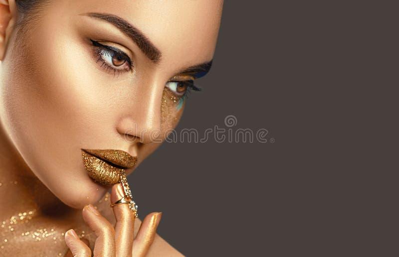 De make-up van de manierkunst Portret van schoonheidsvrouw met gouden huid Glanzende professionele make-up stock foto