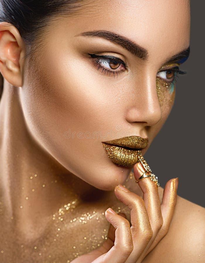 De make-up van de manierkunst Portret van schoonheidsvrouw met gouden huid Glanzende professionele make-up royalty-vrije stock foto's