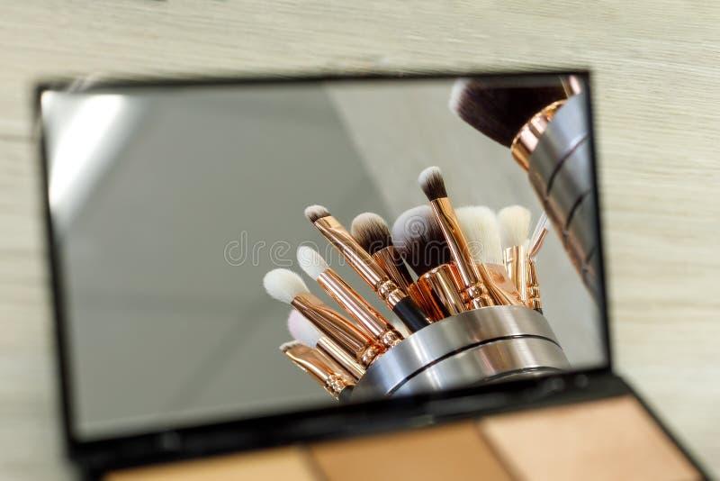 De make-upborstels worden weerspiegeld in een paletspiegel met schaduwen royalty-vrije stock afbeeldingen