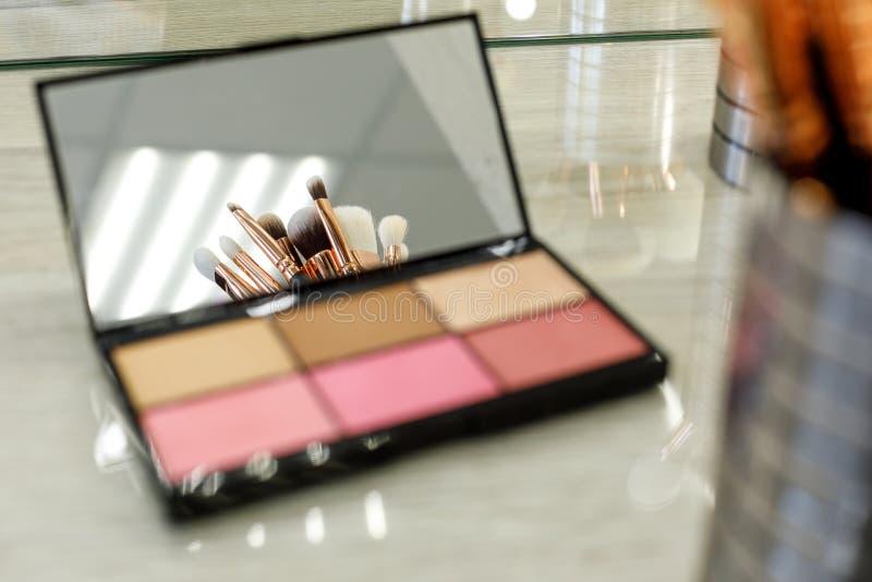 De make-upborstels worden weerspiegeld in een paletspiegel met schaduwen royalty-vrije stock afbeelding