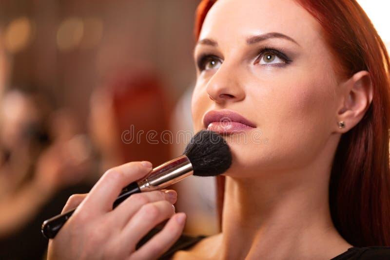 De make-upkunstenaar die vloeibare toon- stichting op het gezicht van de vrouw in wit toepassen maakt omhoog ruimte Schoonheid en stock foto