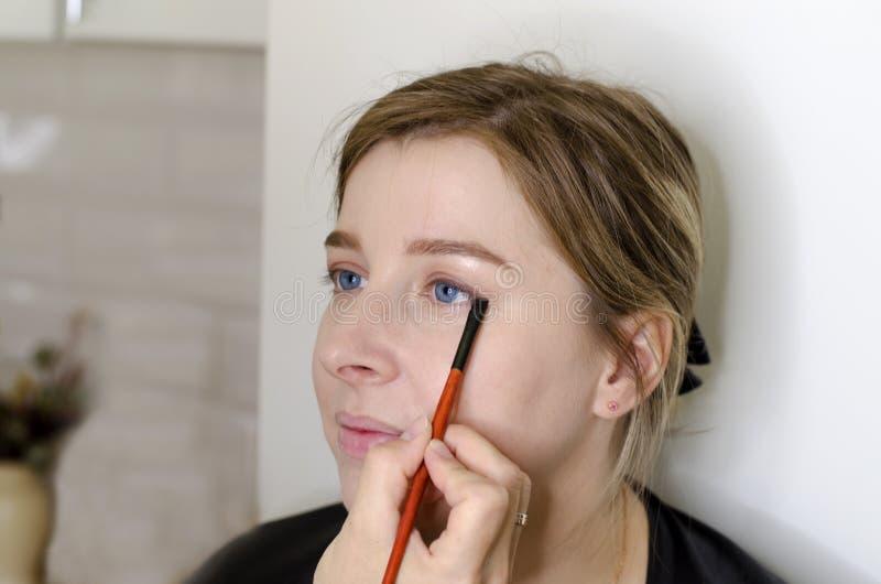 De make-upkunstenaar doet make-up voor het meisje stock afbeelding