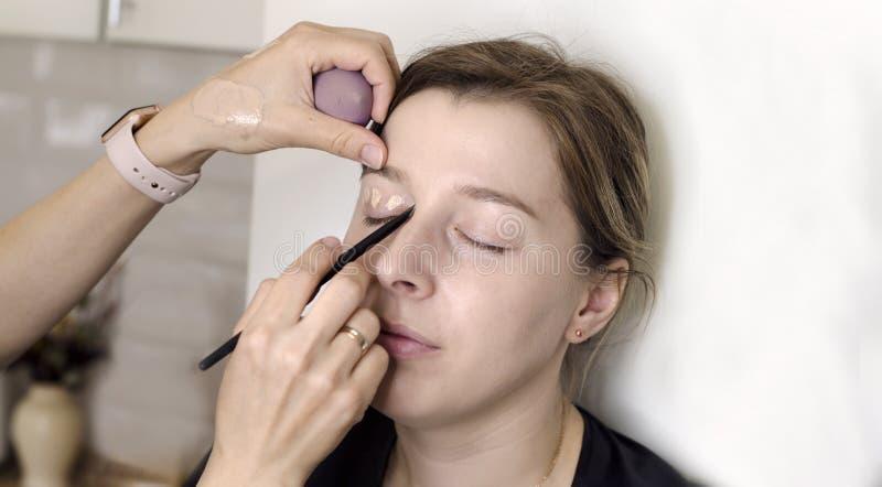 De make-upkunstenaar doet make-up voor het meisje stock afbeeldingen