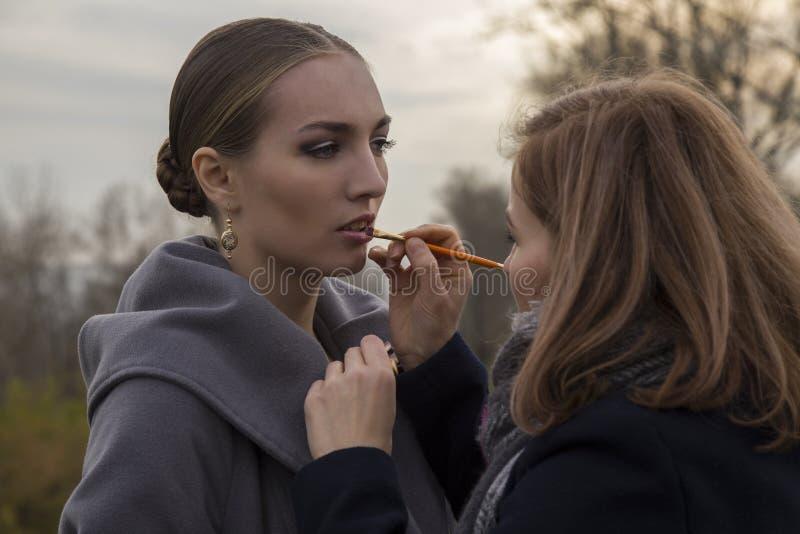 De make-upkunstenaar maakt mooie model openlucht goedmaken vervenlippen met een borstel royalty-vrije stock foto