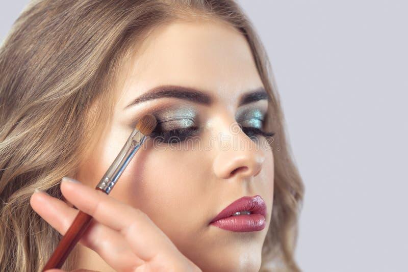 De make-upkunstenaar maakt rokerige ogenmake-up stock afbeelding