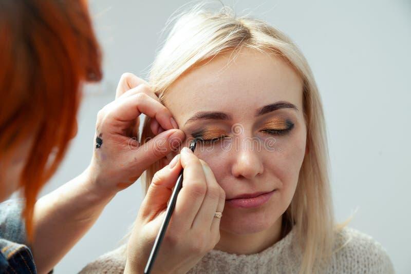 De make-upkunstenaar met een borstel in de handen met een vlakke rand schildert de pijl op het ooglid van het model, toepast same stock afbeeldingen