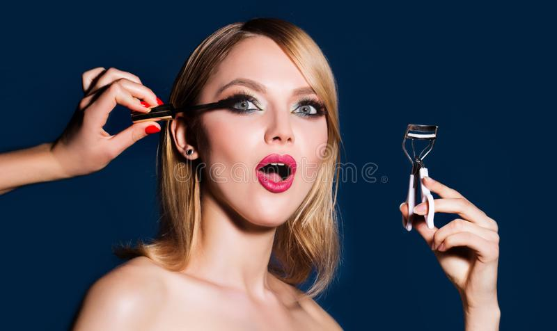 De make-upkunstenaar past mascara op de wimpers toe Heldere rode lippenmake-up, perfecte schone huid, oogschaduwwen Vrouw die haa stock fotografie