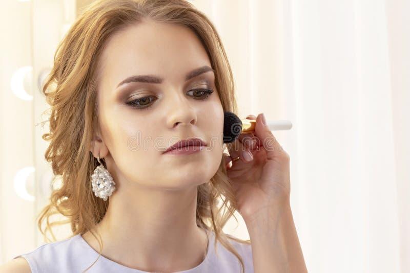 De make-upkunstenaar past mooi modelpoeder toe en bloost met grote borstel op gezicht royalty-vrije stock foto