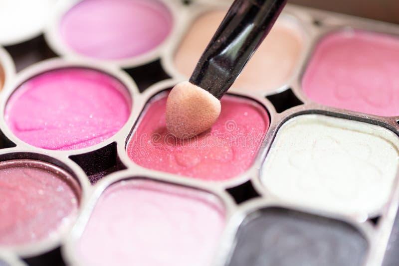 De make-upkunstenaar past Mooi vrouwengezicht toe stock afbeeldingen