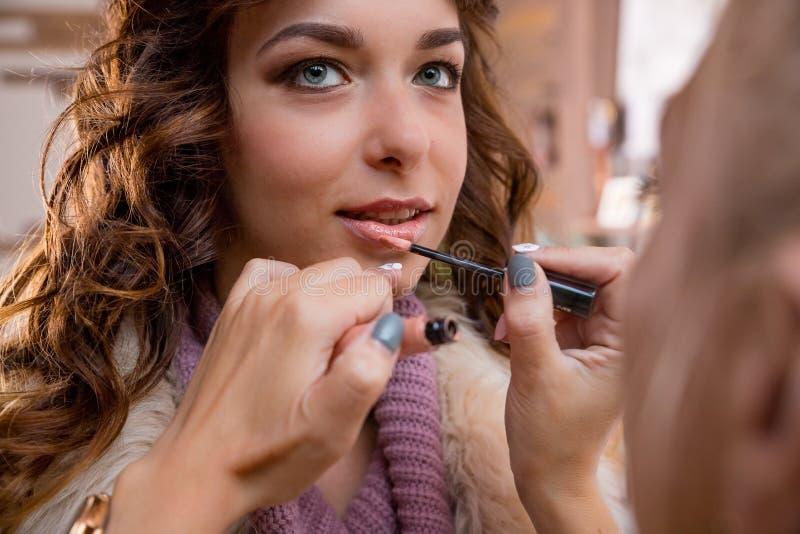 De make-upkunstenaar past rode lippenstift toe Mooi vrouwengezicht Hand van samenstellingsmeester, het schilderen lippen van jong royalty-vrije stock foto