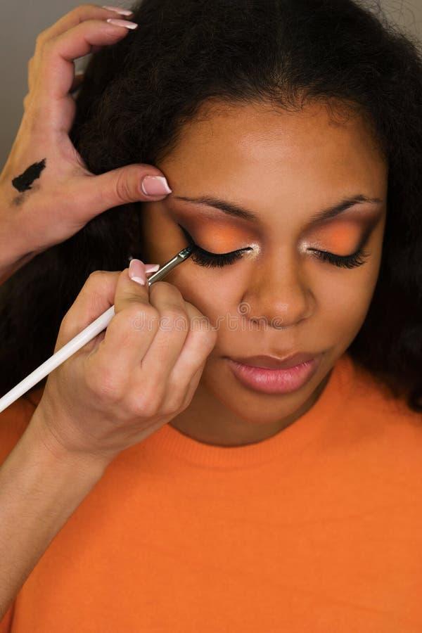 De make-upkunstenaar past make-up op gezicht van meisje toe royalty-vrije stock afbeeldingen